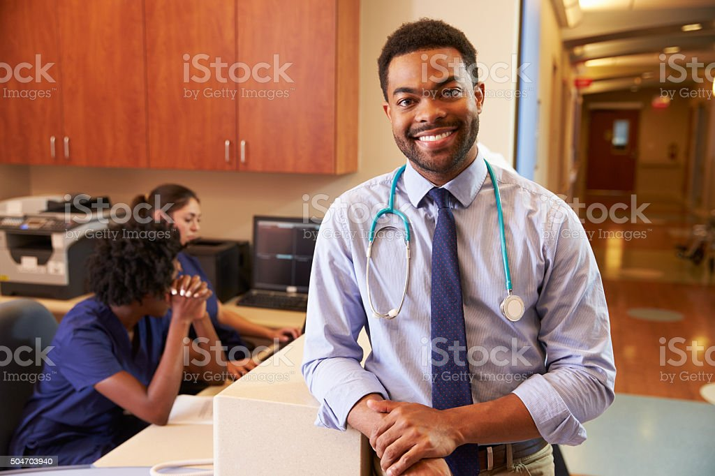 Portrait Of Male Doctor At Nurse's Station In Hospital stock photo