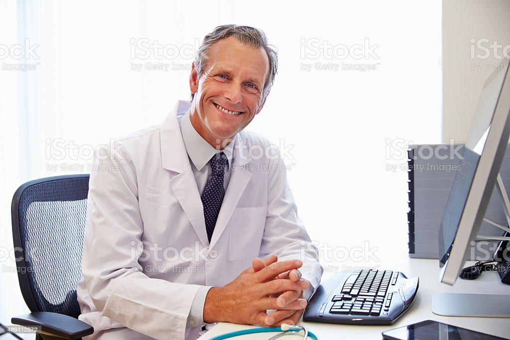 Portrait Of Male Doctor In Office Working At Computer stock photo