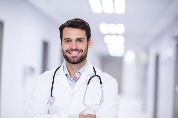 Portrait of male doctor standing with arms crossed stock photo