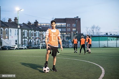istock Portrait of male footballer on pitch with foot on ball and team mates in background 963295616