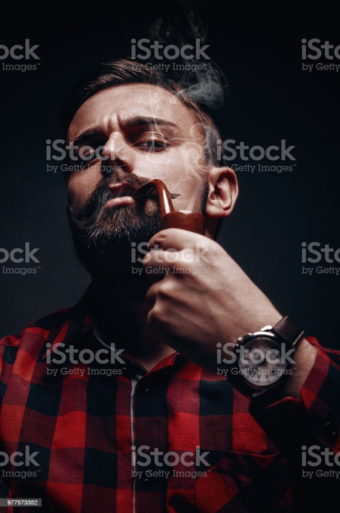 Portrait of male lumber jack model with beard and mustache smoking pipe stock photo