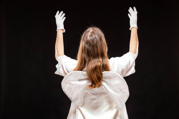 Portrait of male mime artist, isolated on black background. Back view of a man dressed like an angel standing with his hands risen. Symbol of invoke, plead, pray stock photo
