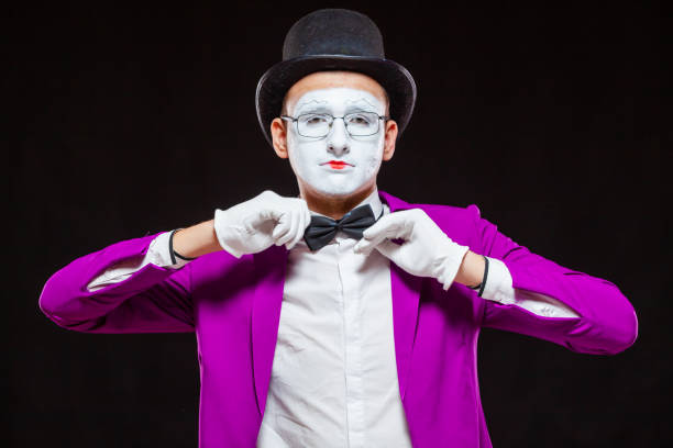 Portrait of male mime artist, isolated on black background. Close up of man face. Man adjusts his bow tie stock photo