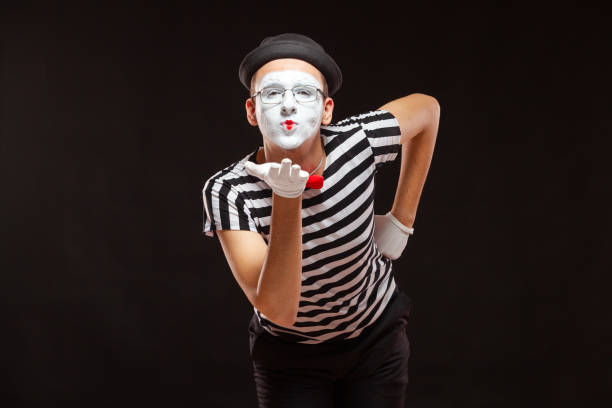 Portrait of male mime artist performing, isolated on black background. Man leaned over to blow a kiss stock photo