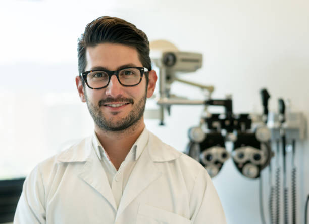 Portrait of male opthalmologist looking at camera smiling and a phoropter at the background stock photo