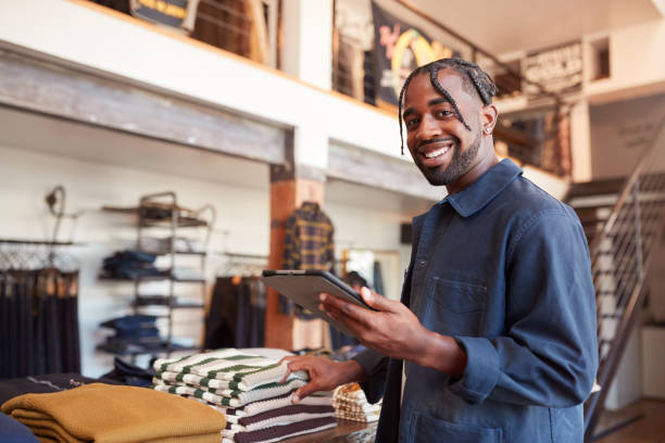 Portrait Of Male Owner Of Fashion Store Using Digital Tablet To Check Stock In Clothing Store stock photo
