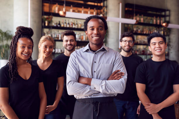 Portrait Of Male Owner Of Restaurant Bar With Team Of Waiting Staff Standing By Counter stock photo