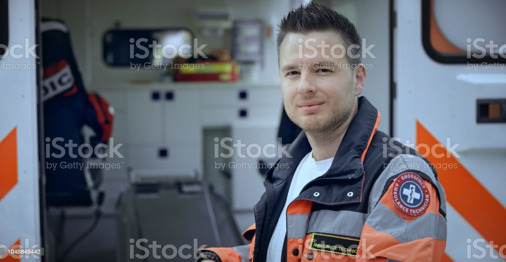 Portrait of male paramedic standing next to ambulance stock photo