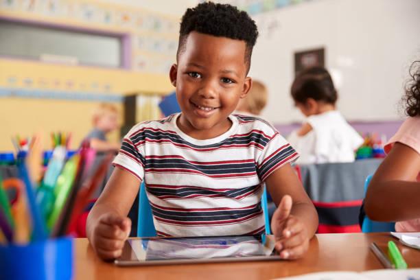 Retrato de alumno masculino en el dibujo de la escuela primaria usando la tableta digital en el aula - foto de stock