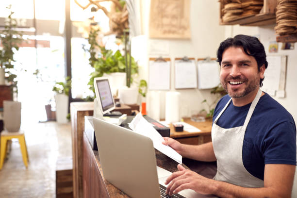 Portrait Of Male Sales Assistant Working On Laptop Behind Sales Desk Of Florists Store stock photo
