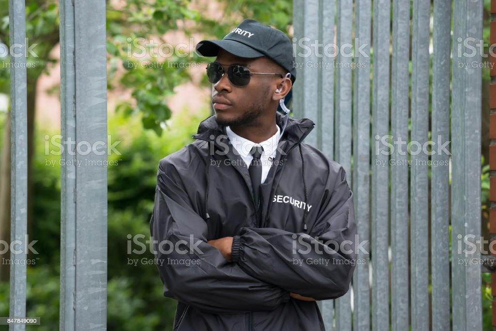 Portrait Of Male Security Guard Standing Arms Crossed stock photo