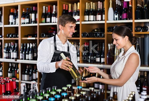 istock portrait of male seller  showing bottle of wine 638485368