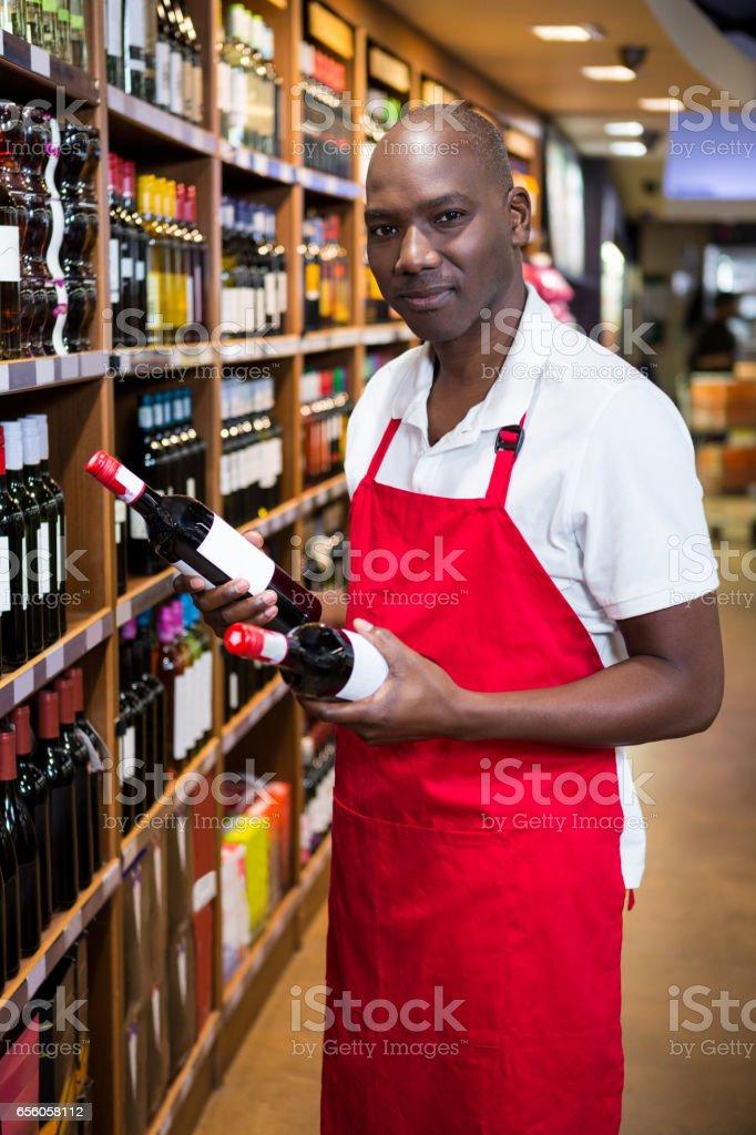 Portret van mannelijke personeel regelen van wijnflessen op plank foto