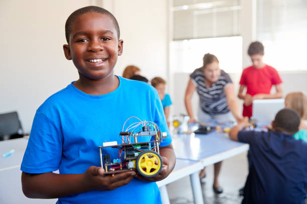 Portrait Of Male Student Building Robot Vehicle In After School Computer Coding Class Portrait Of Male Student Building Robot Vehicle In After School Computer Coding Class middle school teacher stock pictures, royalty-free photos & images