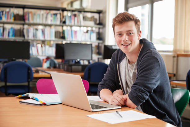 Portrait Of Male Student Working At Laptop In College Library stock photo