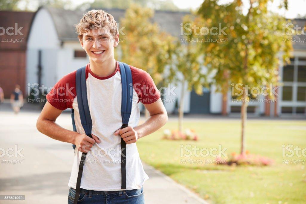 Portrait Of Male Teenage Student Walking Around College Campus stock photo