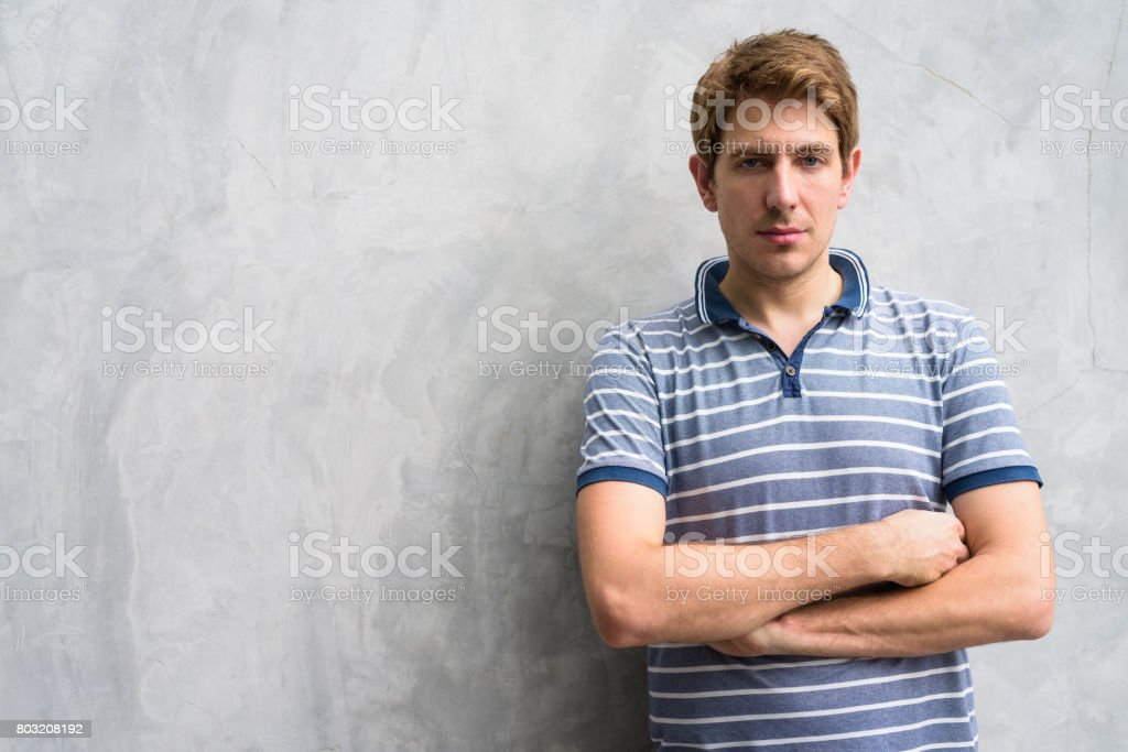 Portrait of man against old concrete wall in the streets outdoors stock photo