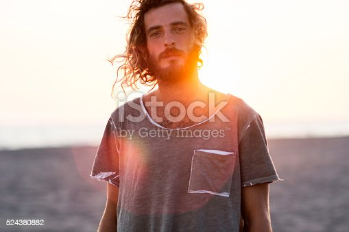 Portrait of young bearded man at the beach