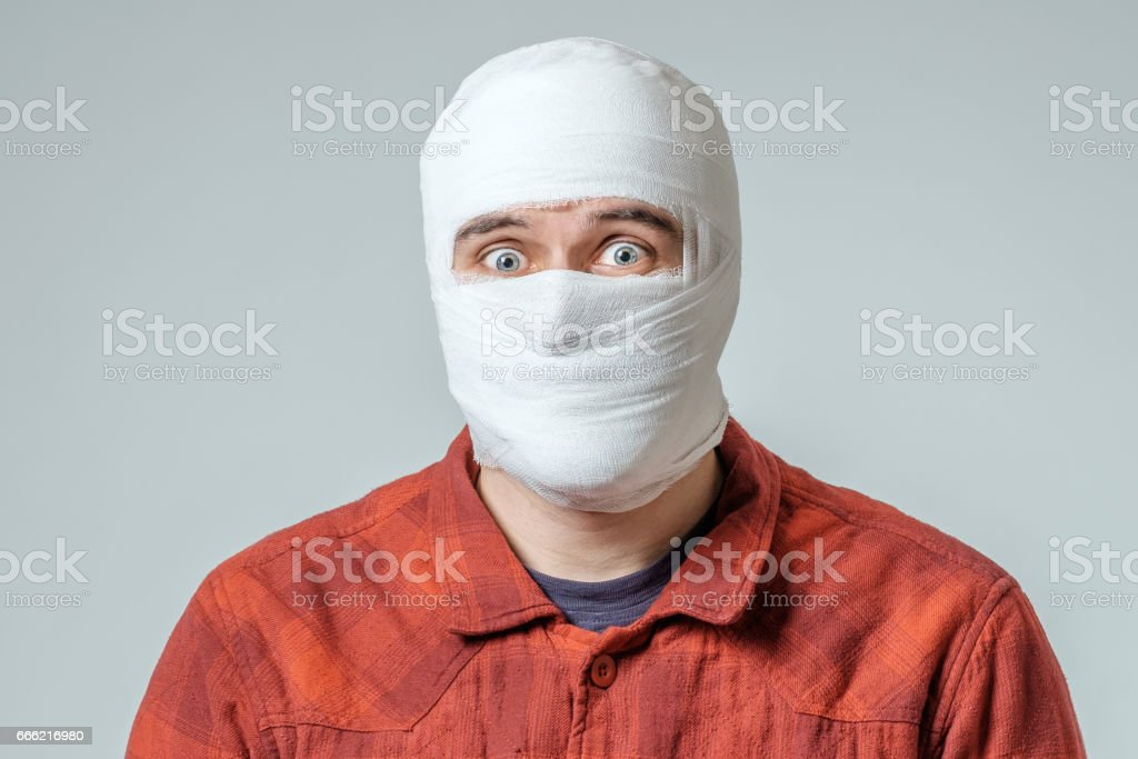Portrait of man bandaged up with a head injury isolated on gray stock photo