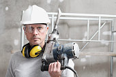 istock portrait of man construction worker with jackhammer with safety hard hat, hearing protection headphones and protective glasses. look at the camera isolated on interior building site background 1217730349