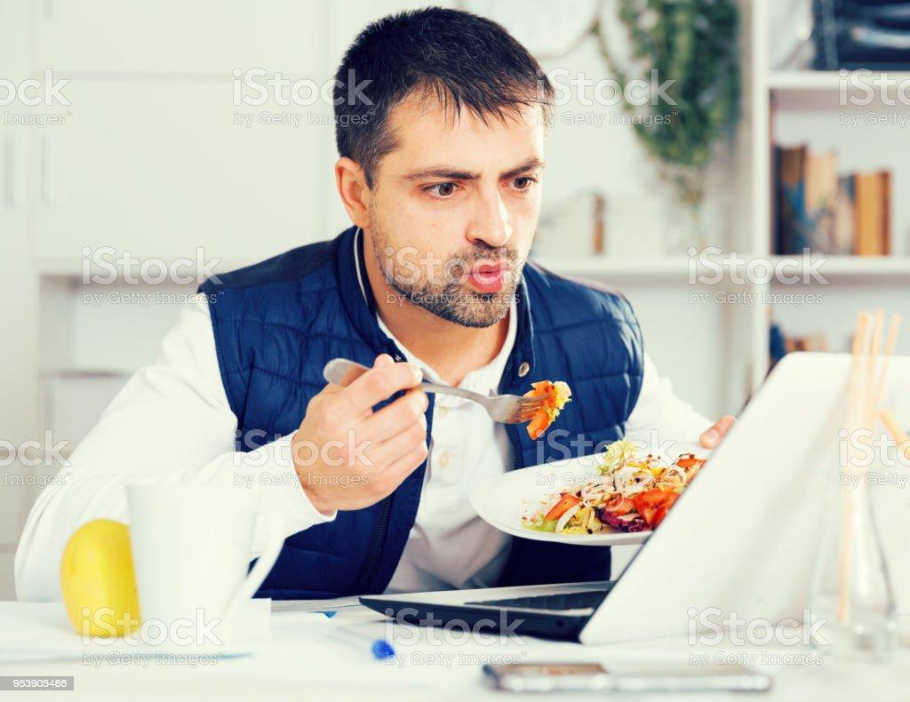 ノート パソコンとテーブルで野菜サラダを食べている男の肖像 ストックフォト