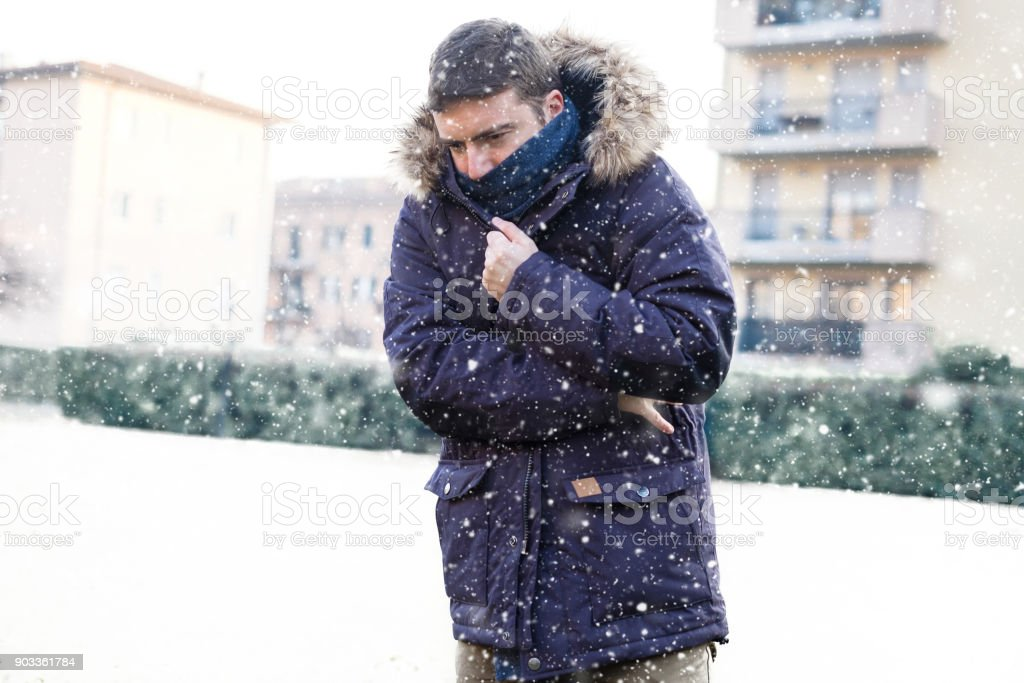 Portrait of man feeling very cold under snowy weather stock photo