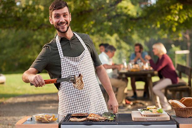 porträt des menschen grillen fleisch auf barbecue im freien - grillschürze stock-fotos und bilder