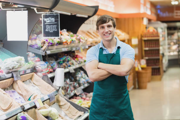 Portrait of man grocer smiling Portrait of man grocer smiling with his arms crossed grocer stock pictures, royalty-free photos & images