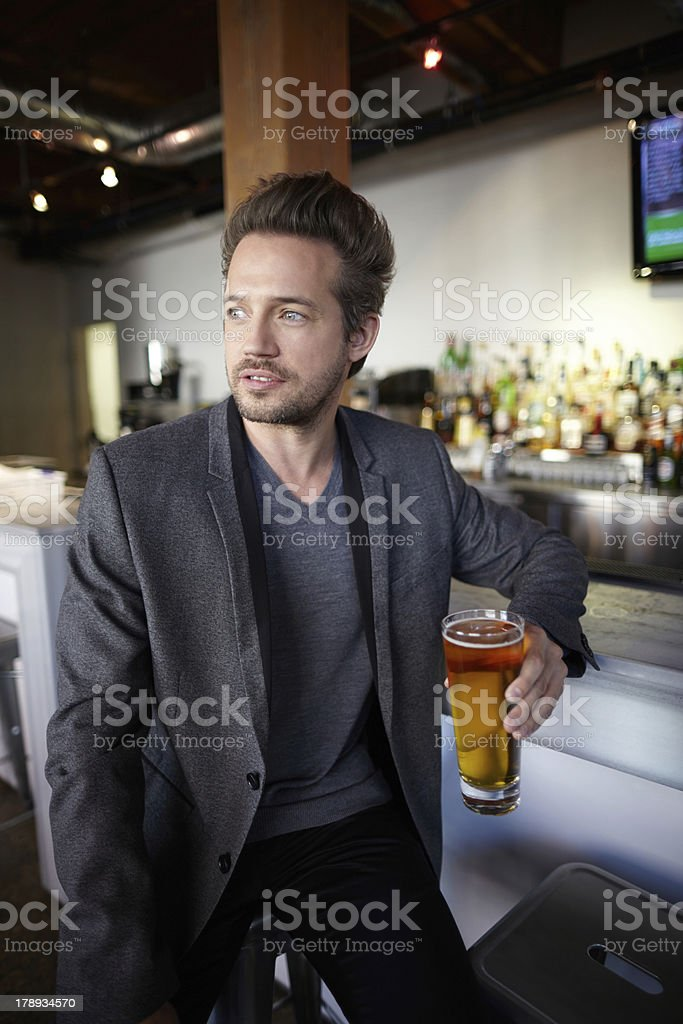 Portrait of man holding beer glass sitting in a bar royalty-free stock photo
