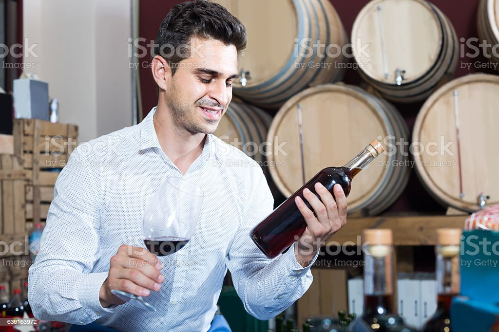 portrait of  man holding bottle and glass of wine stock photo