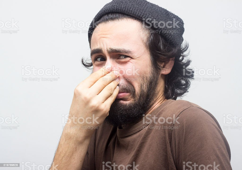 Portrait of man holding his nose in terrified stock photo