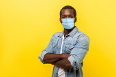 Portrait of man in casual shirt with surgical medical mask standing with crossed hands and looking at camera. medical and healthcare concept.