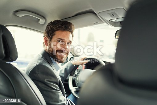 istock Portrait of man in his car. looking camera 492253816
