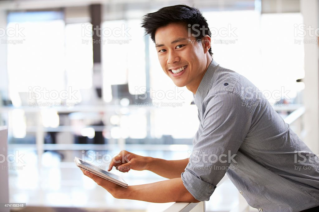 Portrait of man in office using tablet smiling to camera stock photo