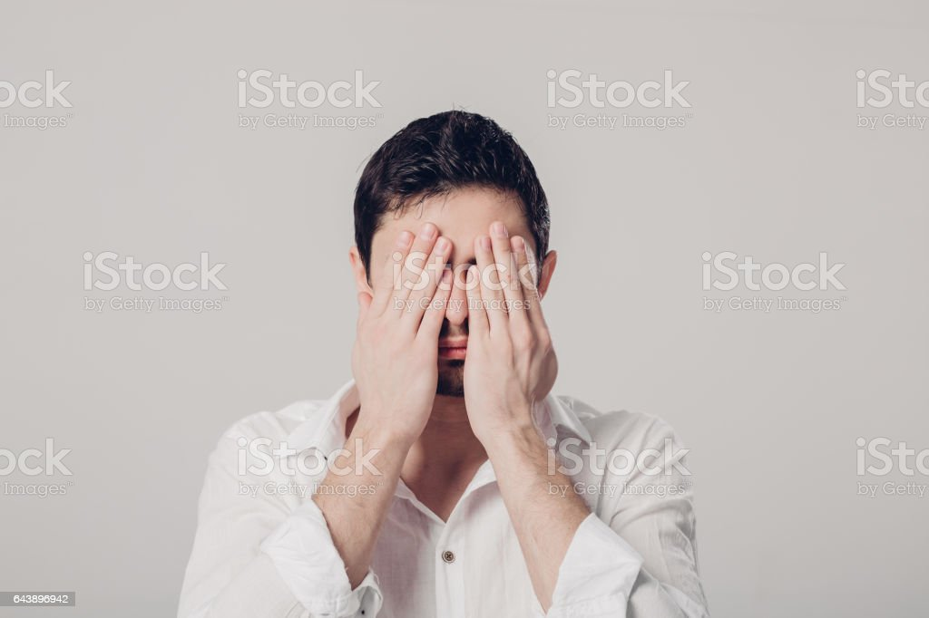 portrait of  man in white shirt closes his eyes with hands on gr stock photo