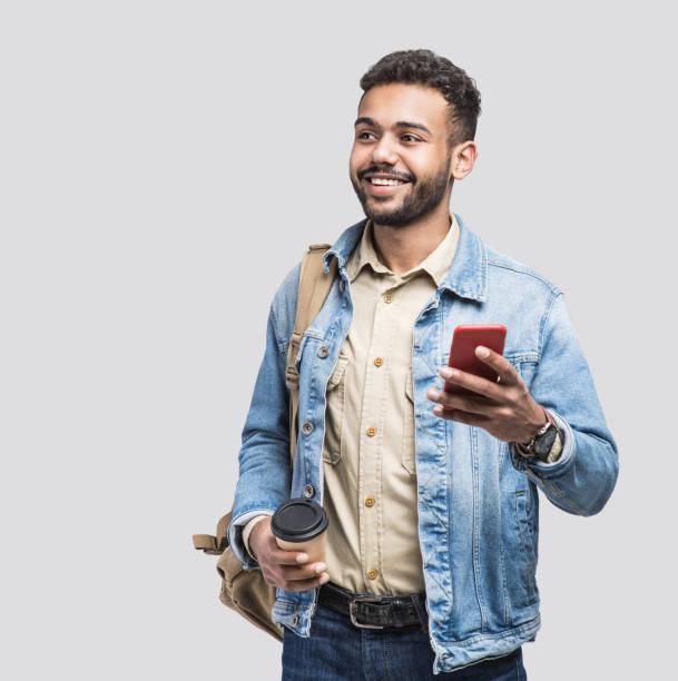 Retrato del estudiante internacional del hombre usando el teléfono inteligente - foto de stock