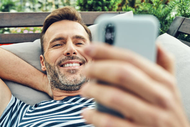 Portrait of man relaxing in the garden and using smartphone stock photo