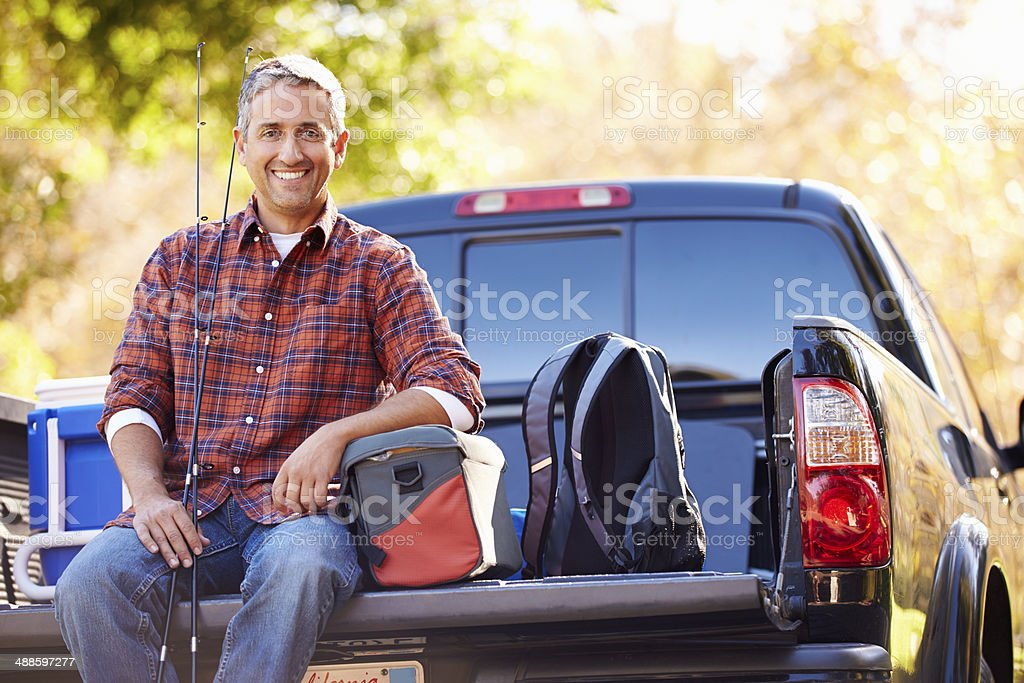 Portrait Of Man Sitting  Pick Up Truck On Camping Holiday stock photo