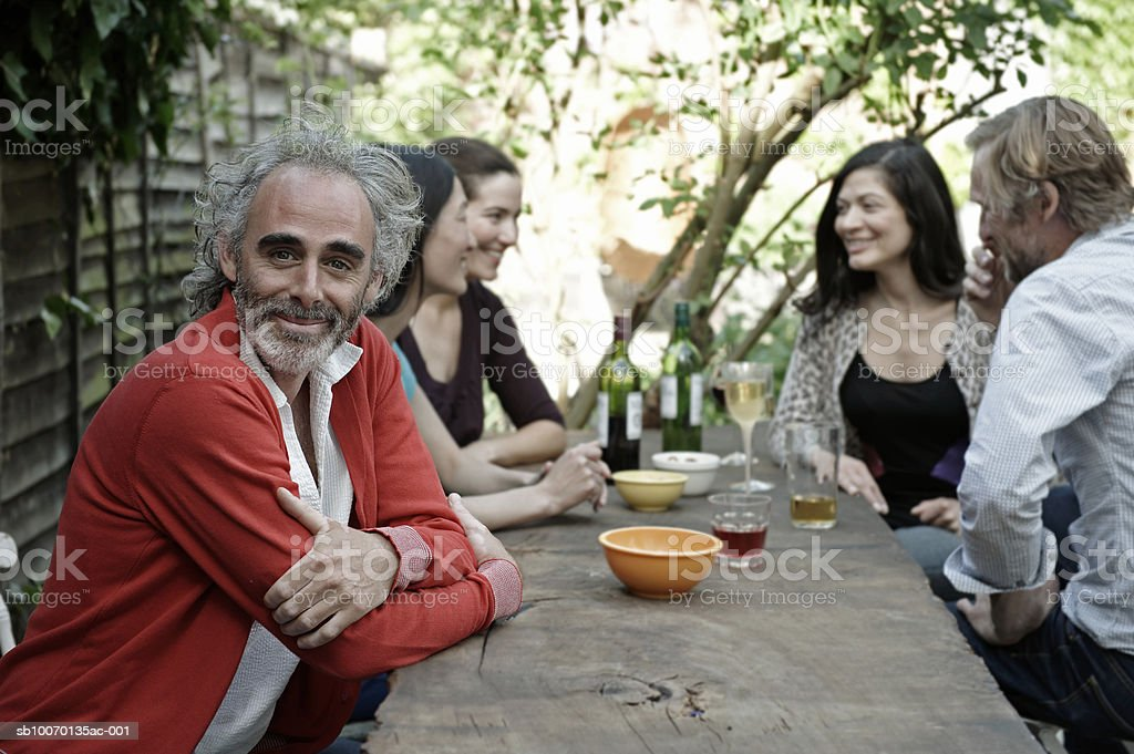 Portrait of man sitting with friends at table in garden royalty free stockfoto