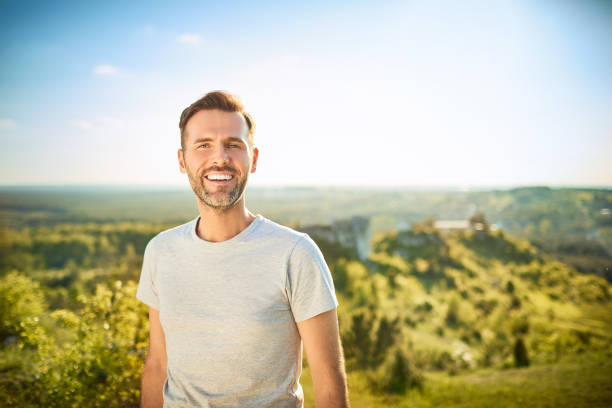 Portrait of man smiling at camera while on trip in the mountains stock photo