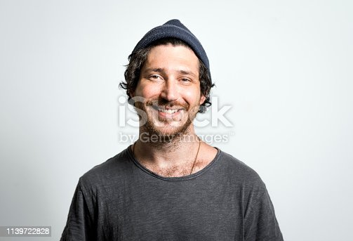 Portrait of mid adult man wearing knit hat and smiling. Handsome male is wearing t-shirt. Hipster is on gray background.
