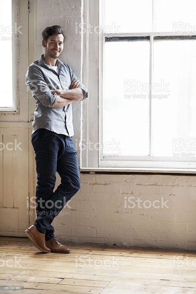 Portrait of man standing by window stock photo