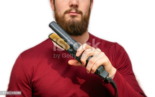Portrait of man straightened his beard with a straightener, styling his beard on isolated white background close-up