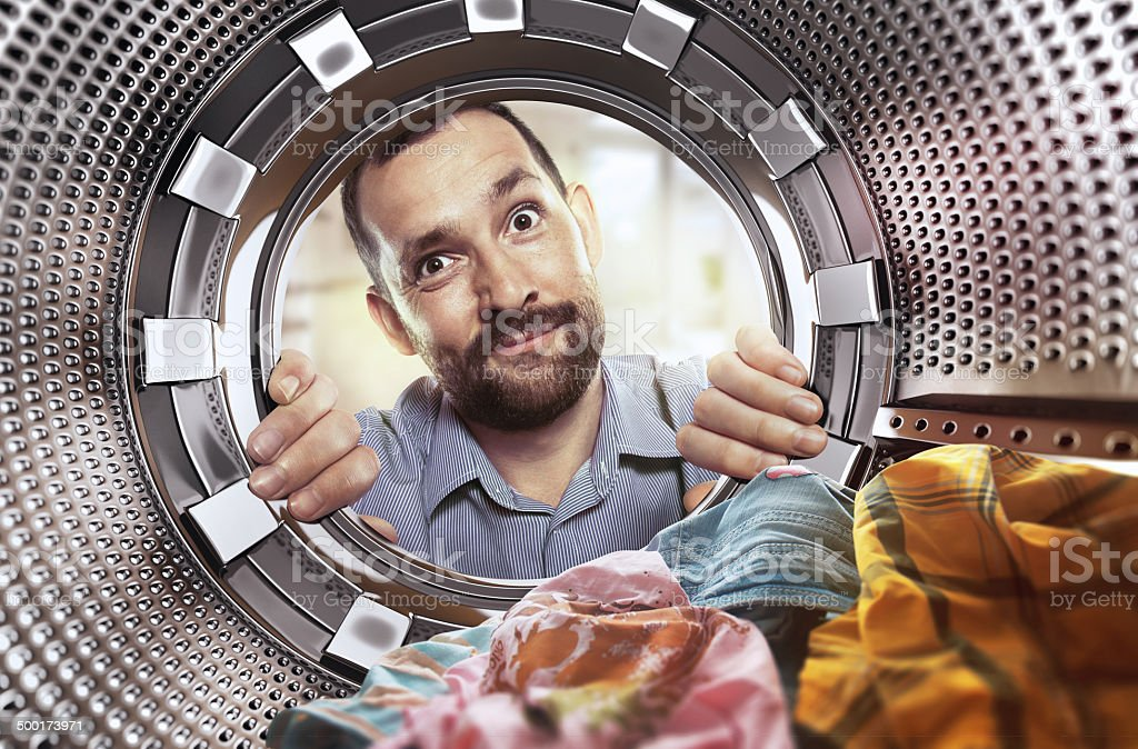 portrait of man view from washing machine inside stock photo