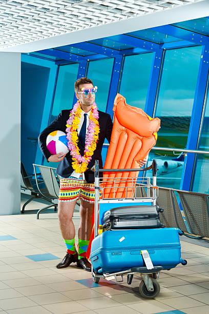 portrait d'un homme portant veste short de plage et à l'aéroport - valise humour photos et images de collection
