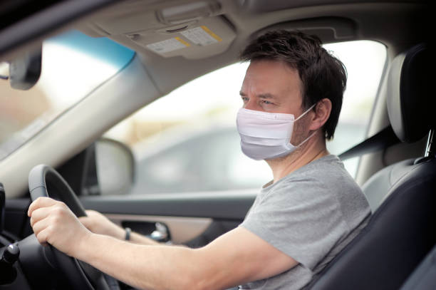Portrait of man wearing disposable medical facemask in a car during coronavirus outbreak. stock photo