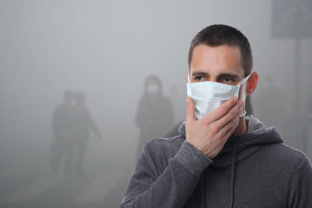 Portrait of man wearing facial hygienic mask outdoors. Ecology, air pollution, Environmental awareness and virus protection concept stock photo