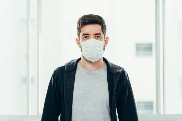 Porträt des Mannes, der chirurgische Maske zu Hause trägt. Covid-19, Coronavirus und Quarantänekonzept. – Foto