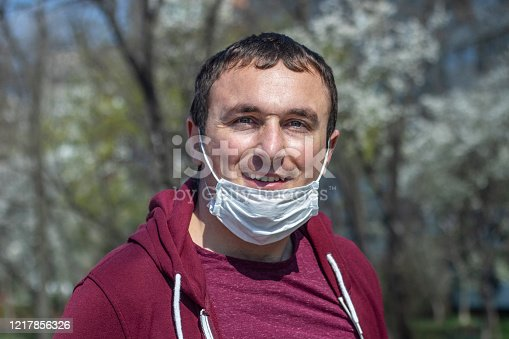 Portrait of man wearing surgical mask on chin. Masking policy concept.