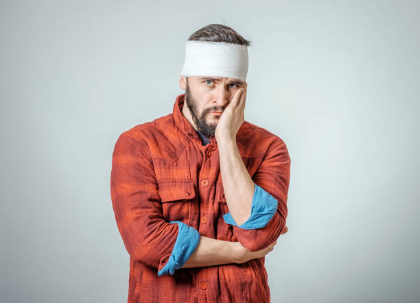 portrait of man with bandages wrapped around his head isolated on gray background - head injury stock photos and pictures